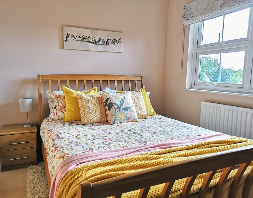 Newly renovated pink master bedroom with mustard accents.
