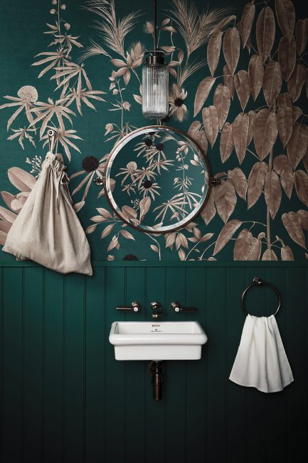 Beautiful dark green downstairs cloakroom with contrasting floral wallpaper.