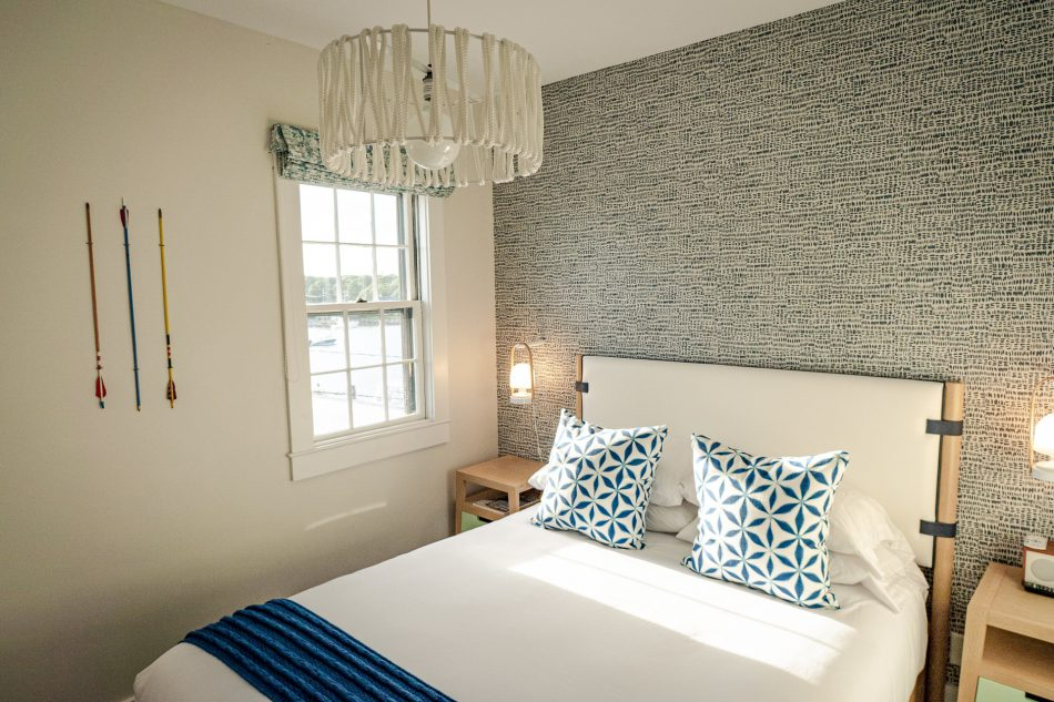Staging a master bedroom with a striking but not overpowering feature wall, and blue accents in the bedding.
