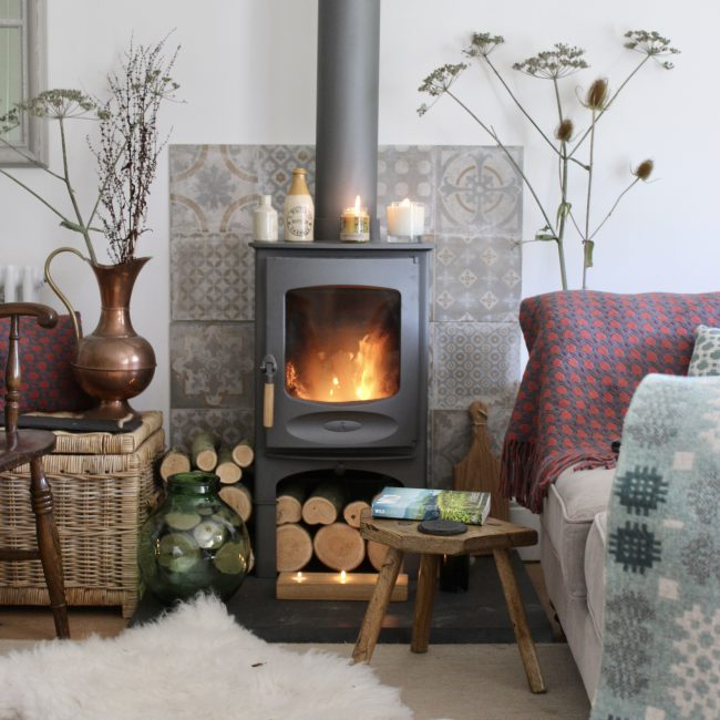 Autumn fireside - log burner with soft woollen throws on a sofa.