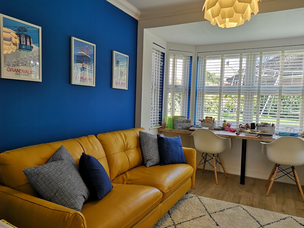Bright blue wall and yellow sofa in new family room
