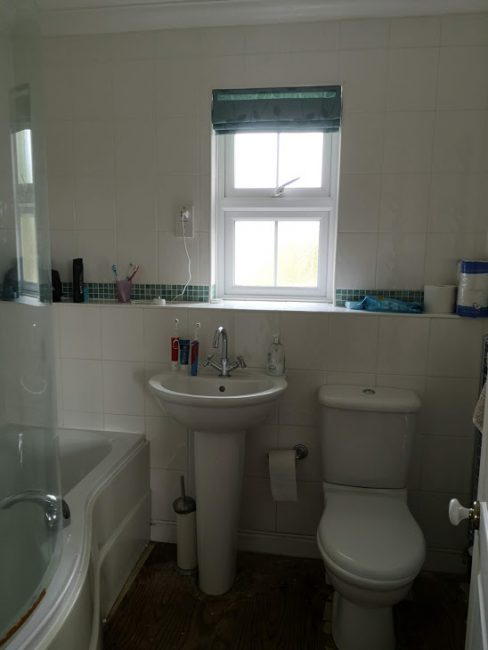 Family bathroom pre renovation with white tiles floor to ceiling and broken toilet.