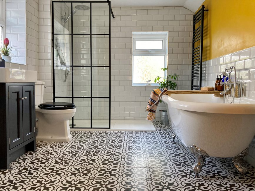 Bathroom with victorian style floor tiles and a bright yellow wall.